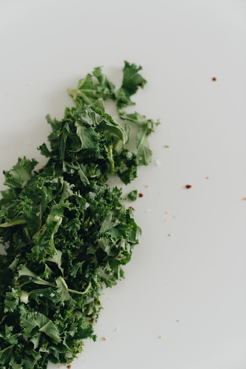 Close-Up Photo of Kale Leaves on a White Surface