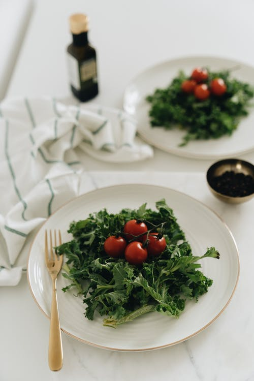 Close-Up Photo of Two Kale Leaves with Cherry Tomatoes on a White Plate
