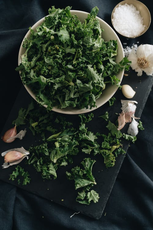 Close-Up Photo of a Bowl of Kale Leaves Near Garlic