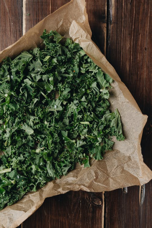 Overhead Shot of Green Kale Leaves on a Wooden Surface