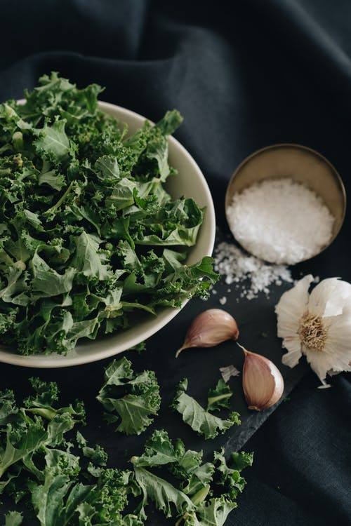 Photo of Kale Leaves on a Bowl Near Garlic and Salt