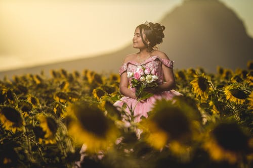 Young ethnic woman in romantic dress among sunflowers