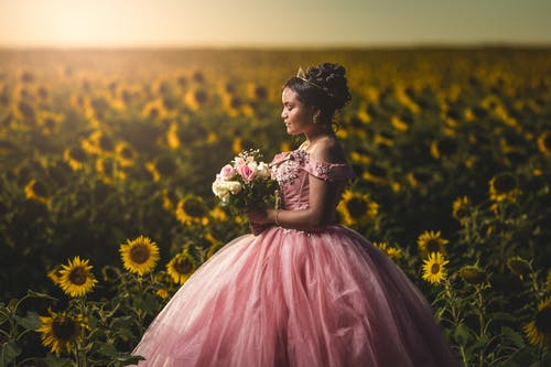 Peaceful young ethnic woman in pink gown standing in sunflower field