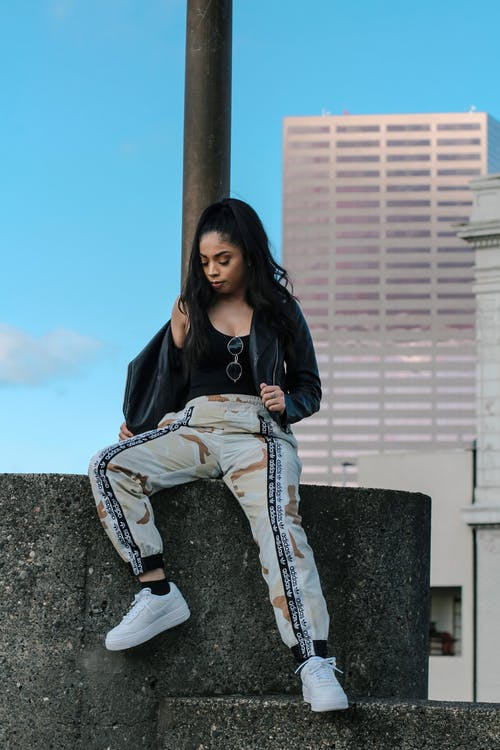 Woman in Black Leather Jacket and Jogger Pants Sitting on Concrete Bench
