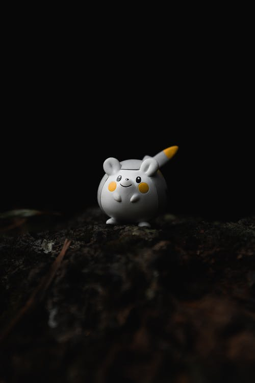 Closeup of small rubber spherical anime character toy placed on rough surface against black background