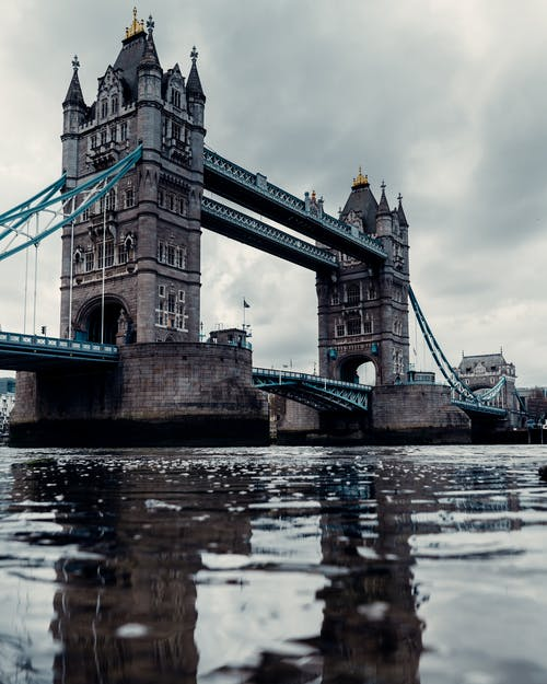 Aged suspension bridge over river in city