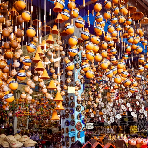 Low angle of various traditional lamps and clay products hanging on stall in local bazaar
