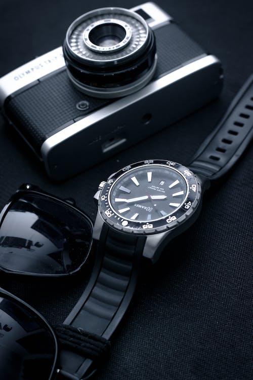 Close-Up Photo Of Watch Beside Analog Camera