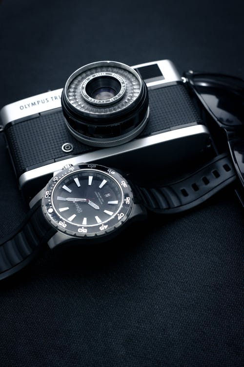 Close-Up Photo Of Watch Beside Camera