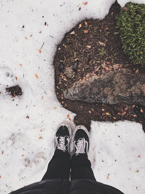 Person in Black Pants and Black and White Sneakers Standing on Snow Covered Ground