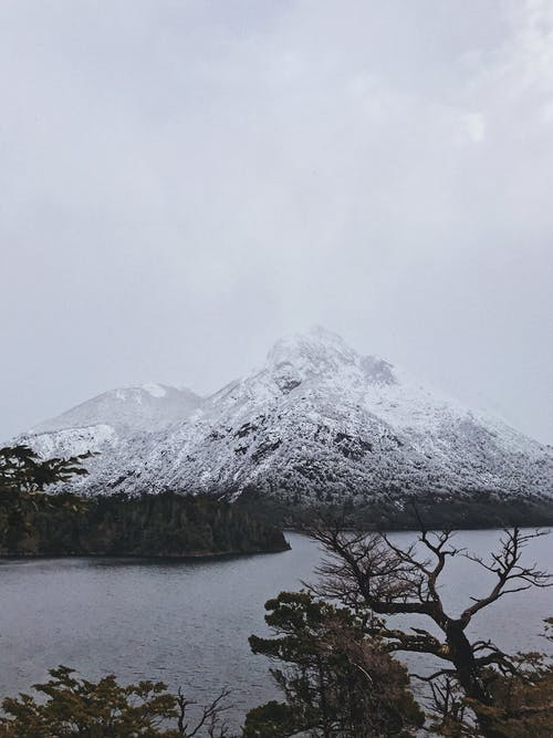 Snow Covered Mountain Near Body of Water
