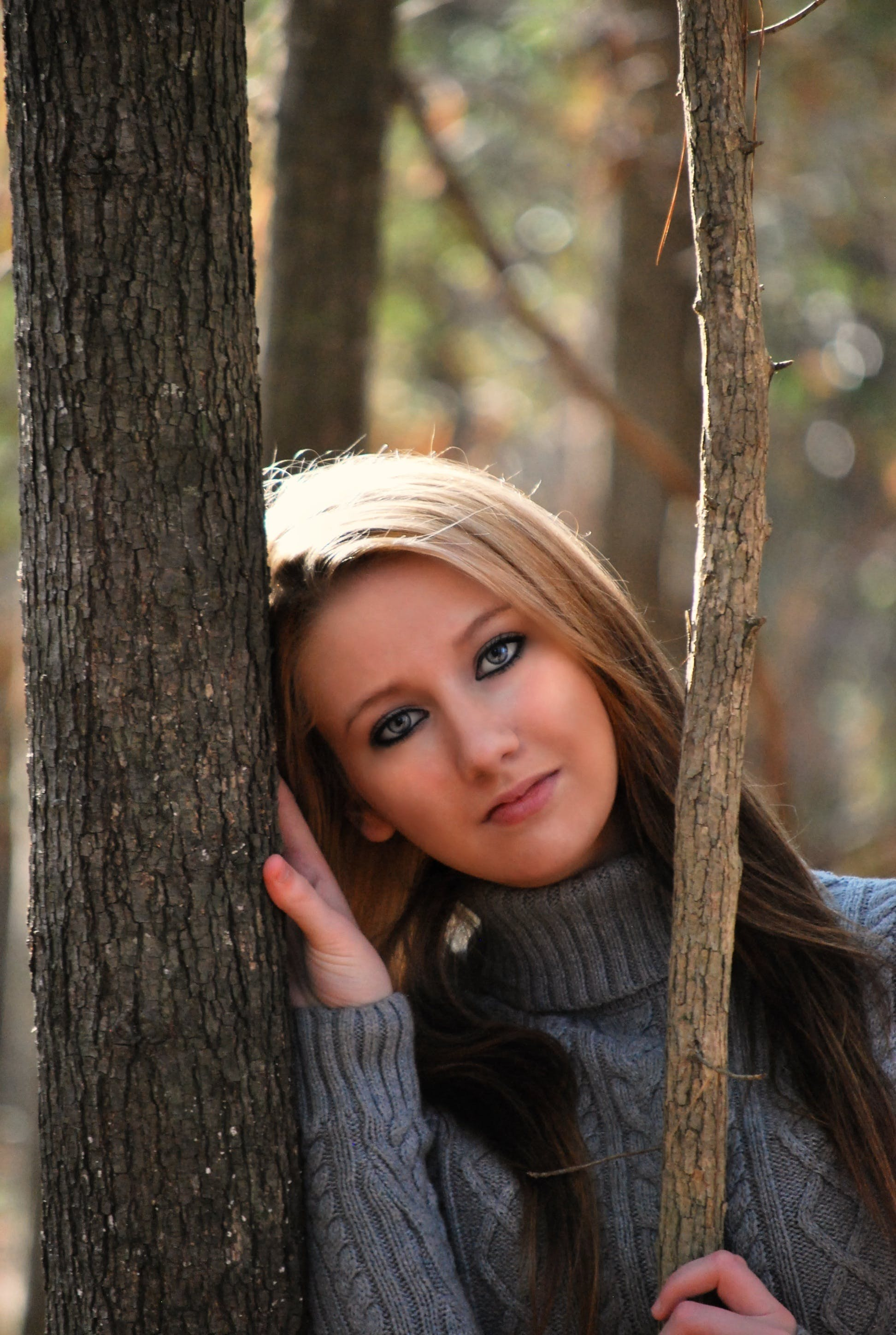 Woman in Grey Sweater Lying on Tree during Daytime