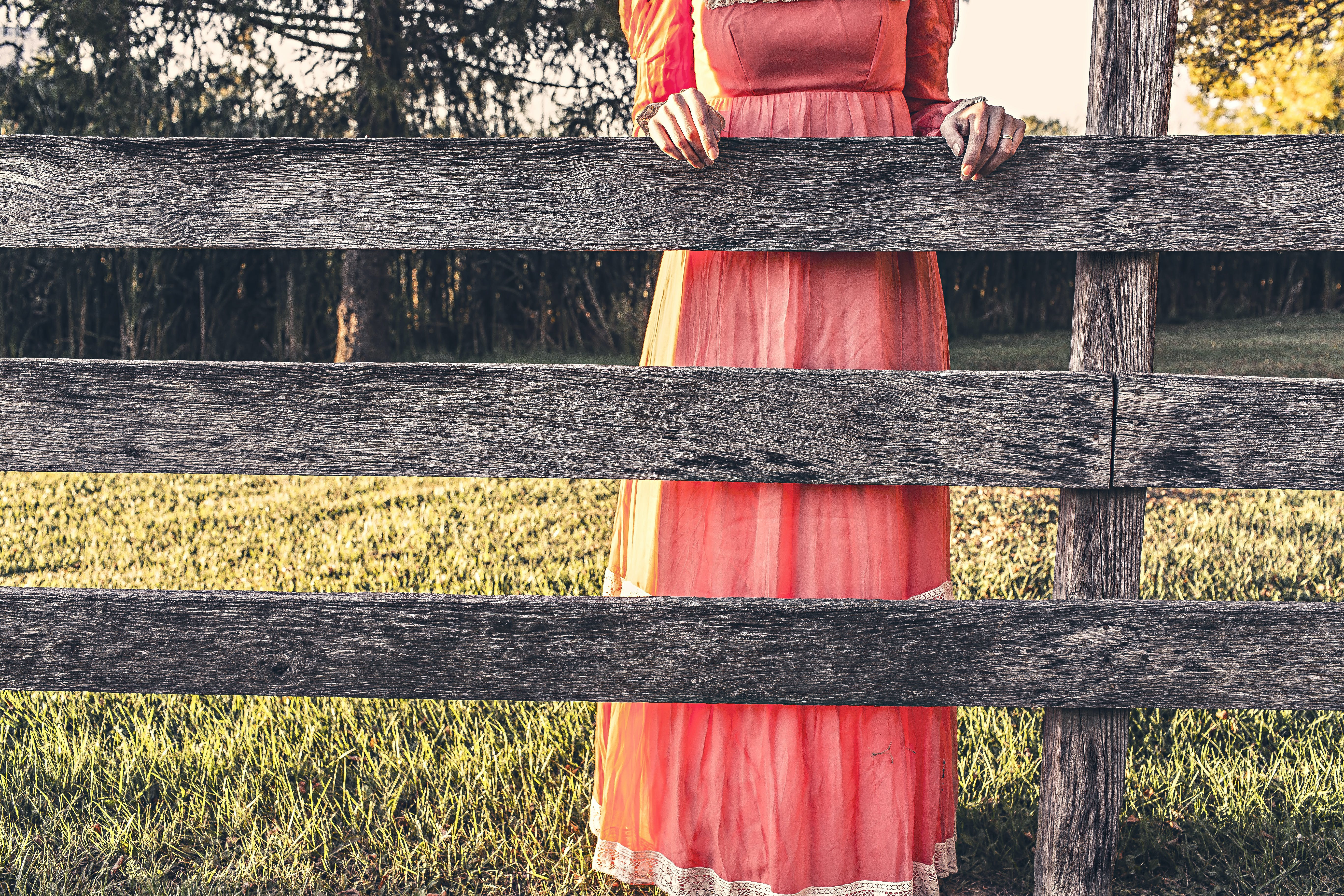 Woman Wearing Red Dress Holding Gray Wooden Fence