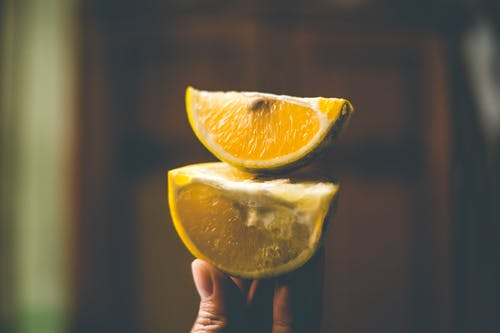 Photo Of Person Holding Sliced Lemon