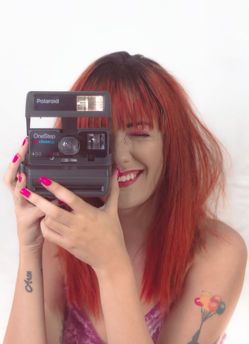 Photo Of Woman Holding Polaroid Camera