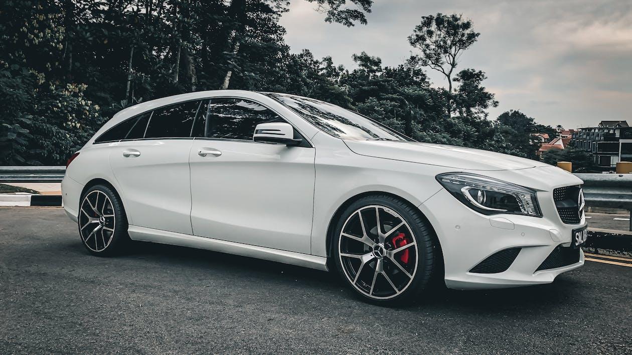 Grayscale Photo of Sedan on Road