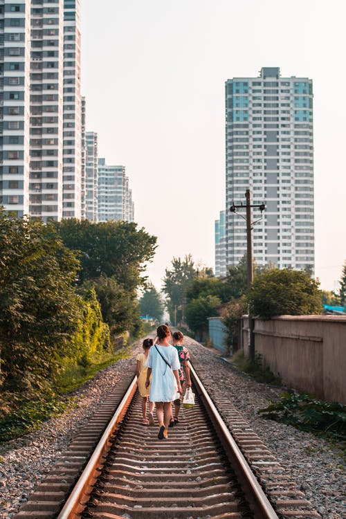 Photo Of People Walking On Railroad