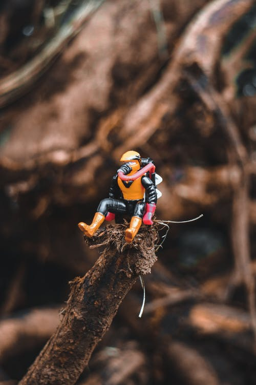 Small comic hero figurine placed on tree trunk
