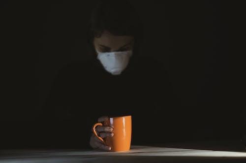 Woman in Black Shirt Holding Orange Ceramic Mug