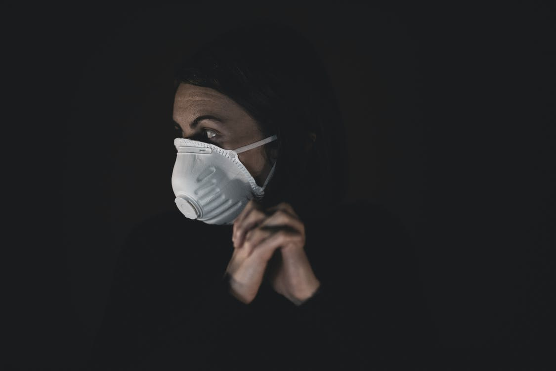 Woman in Black Shirt Wearing White Mask