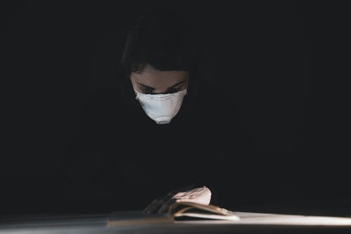 Person in Black Long Sleeve Shirt Wearing N95 Mask While Reading