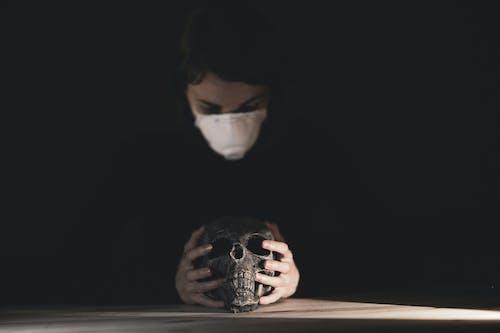 Woman in Black Long Sleeve Shirt Holding Black Skull