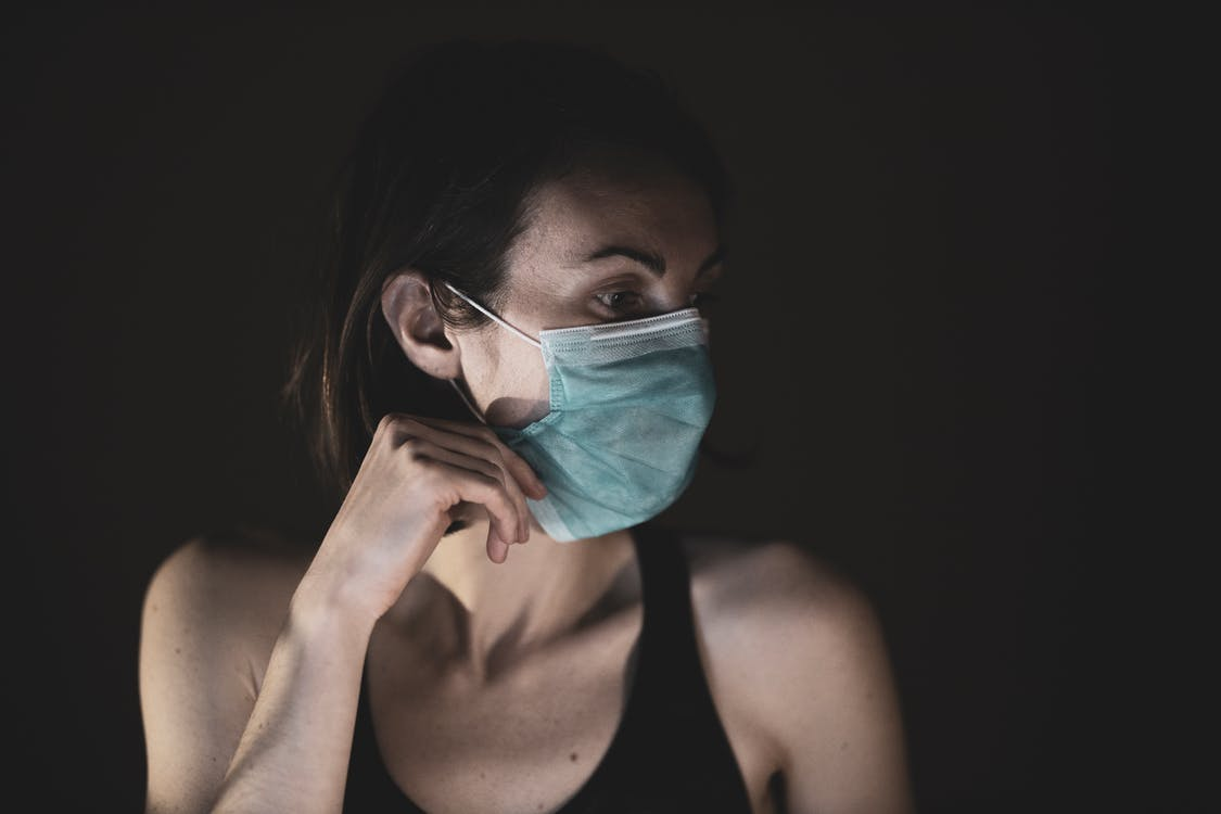 Woman in Black Tank Top Wearing A Surgical Mask