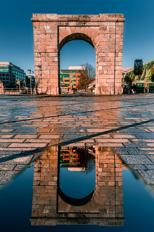 Arched Stone Gateway With Reflection On A Puddle