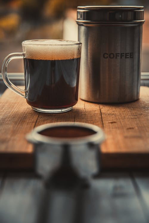 A Glass Of Black Coffee And Coffee Canister On Wooden Table