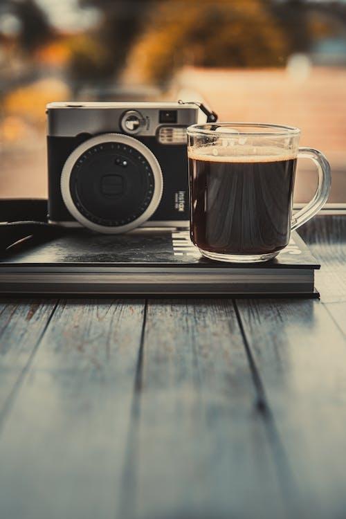 Glass Mug With Coffee Beside An Old Camera