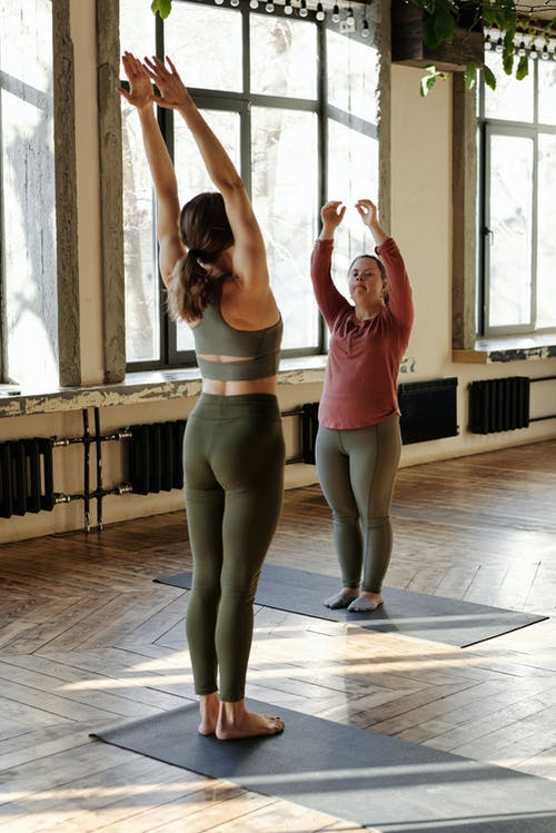 Two Women Exercising With Arms Raised Up