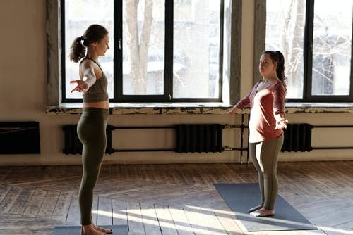 Two Women Exercising With Arms Raised Sidewards
