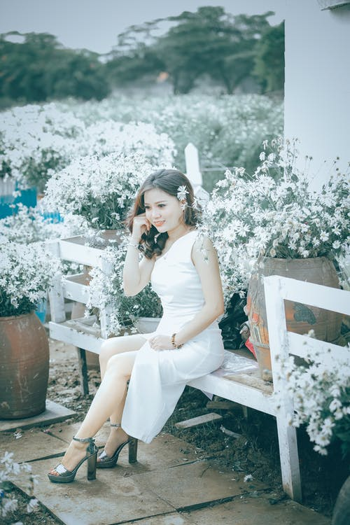 Side view of young happy ethnic female in white dress relaxing on bench among blooming delicate flowers