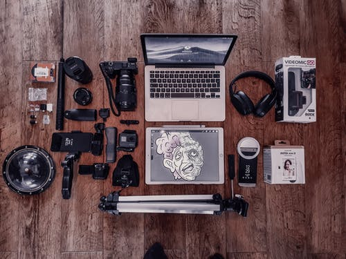 Overhead composition of laptop and graphic tablet composing with photo camera and other different items for freelance and professional photography