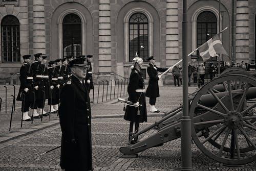 People in Black Coat Standing Near Black Metal Post