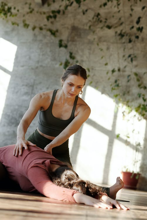 Photo Of A Trainer Supporting A Girl Do Bending Exercise