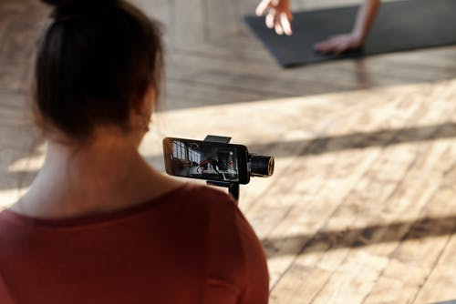 A Girl Taking Video Of A Woman Exercising