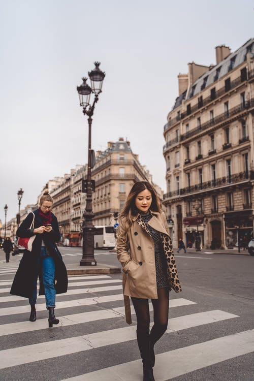 Woman in Brown Coat Walking on Pedestrian Lane