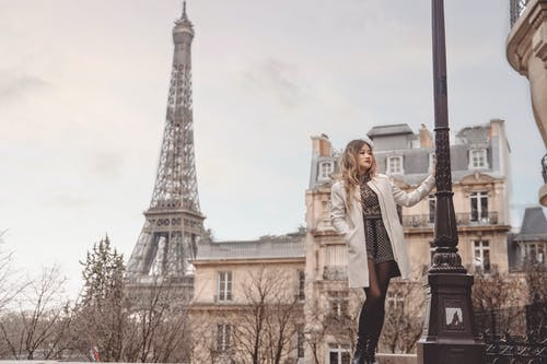 Woman in White Long Sleeve Shirt Standing Near Eiffel Tower