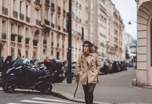 Woman Crossing The Street Wearing A Brown Coat