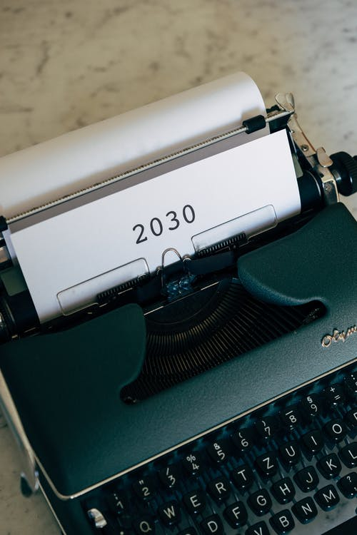 Green and White Vintage Typewriter With White Paper