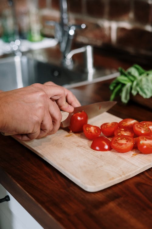 Photo Of Person Slicing Tomatoes