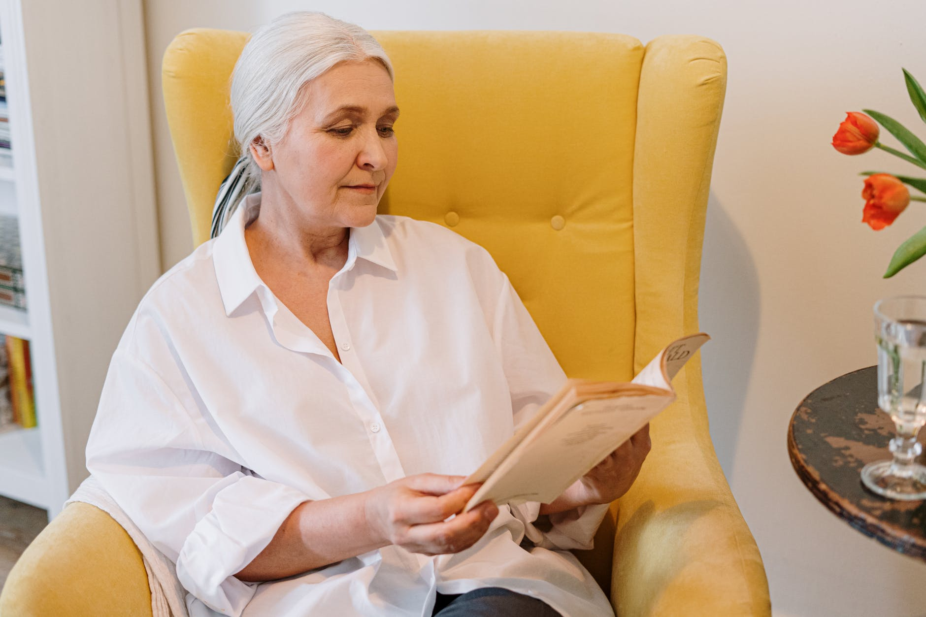 An elderly woman sitting on a couch reading a book. | Photo: Pexels