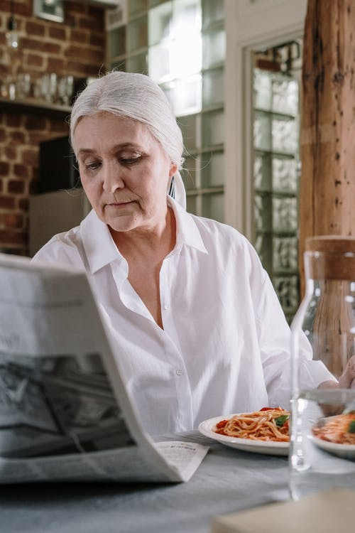 An Elderly Woman Reading The Newspaper While Eating Spaghetti