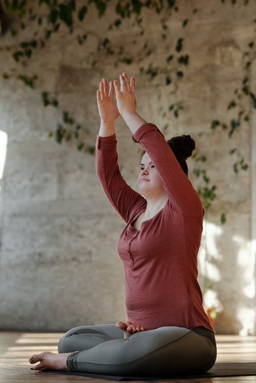 Photo Of Young Woman With Her Arms Raised While In A Sitting Position