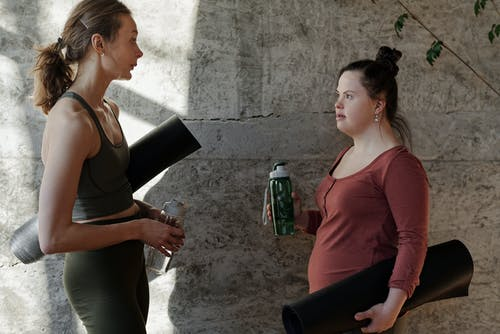 Women Holding Their Water Bottles and Yoga Mats