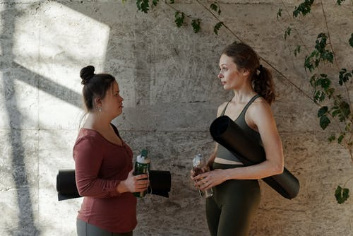 Two Women Holding Water Bottle and Yoga Mat