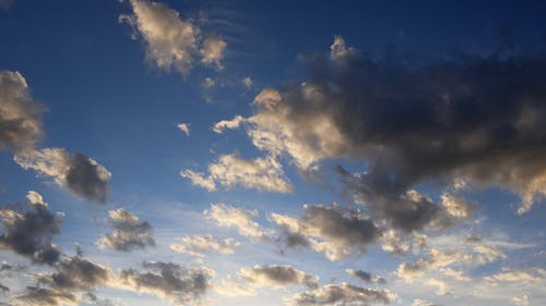 Picturesque from below view of endless blue sky with clouds highlighted by sun