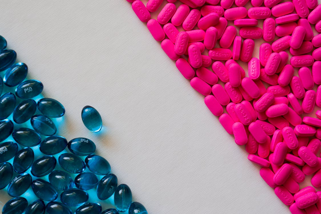 Pink Tablets And Blue Capsules In Close-up View