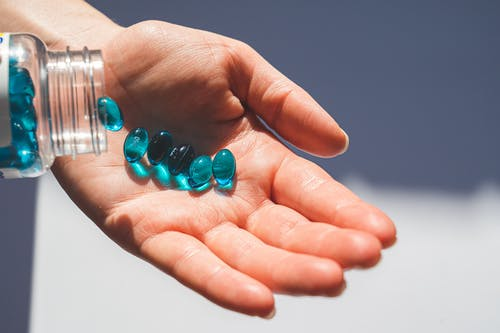 Person Holding Blue Pills